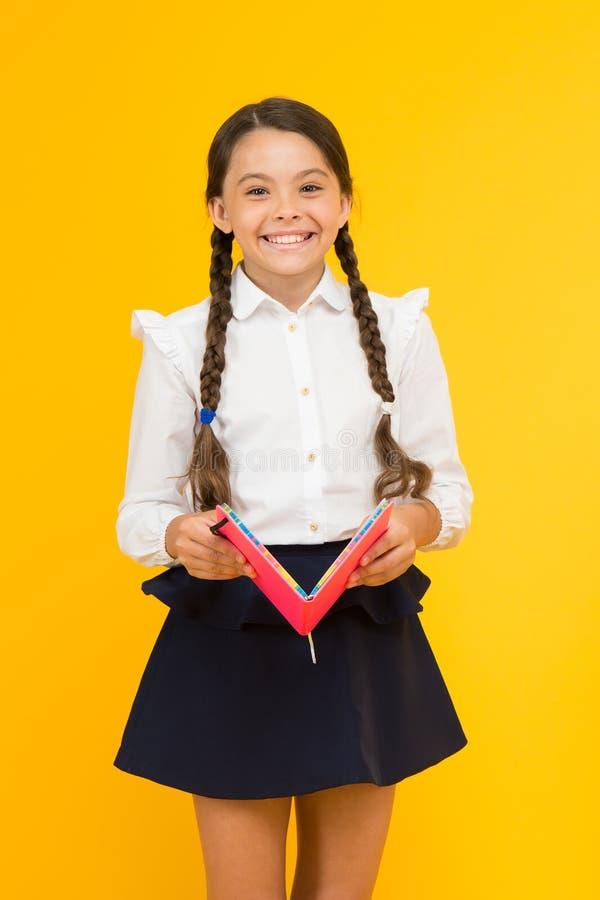 De nouveau au concept d'?cole Livre de prise de fille Fille d'école sur le fond jaune Pratique et améliorer des qualifications de photographie stock libre de droits