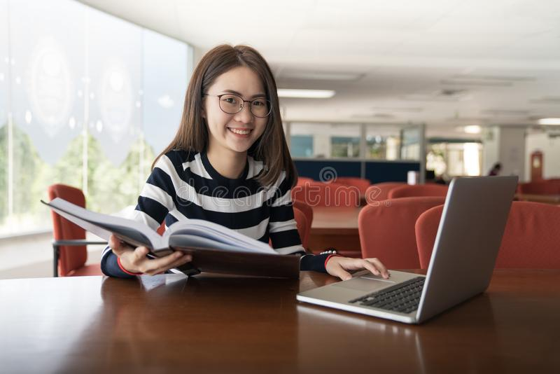 De nouveau au concept d'université d'université de la connaissance d'éducation d'école, aux jeunes femmes travaillant et à l'ordi photo stock