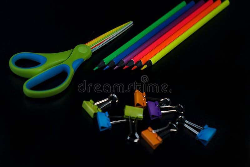 De nouveau au fond d'?cole avec des crayons, ciseaux, trombones color?s sur le contexte noir photo libre de droits