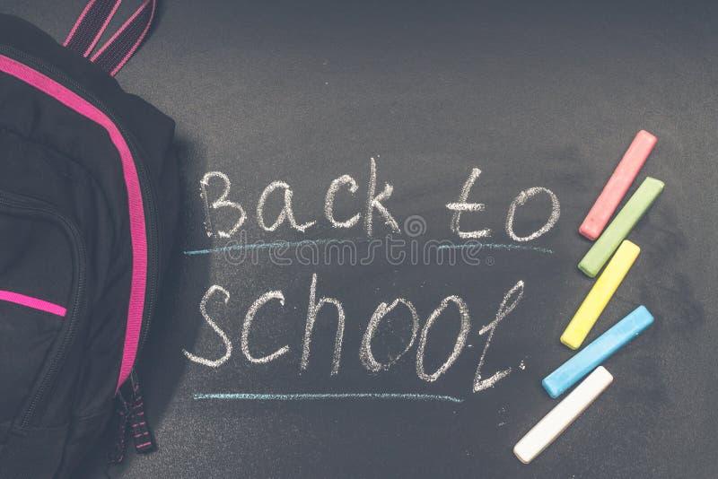 De nouveau au message d'école sur le tableau noir inscrit avec la craie colorée pour le fond baluchon photos stock