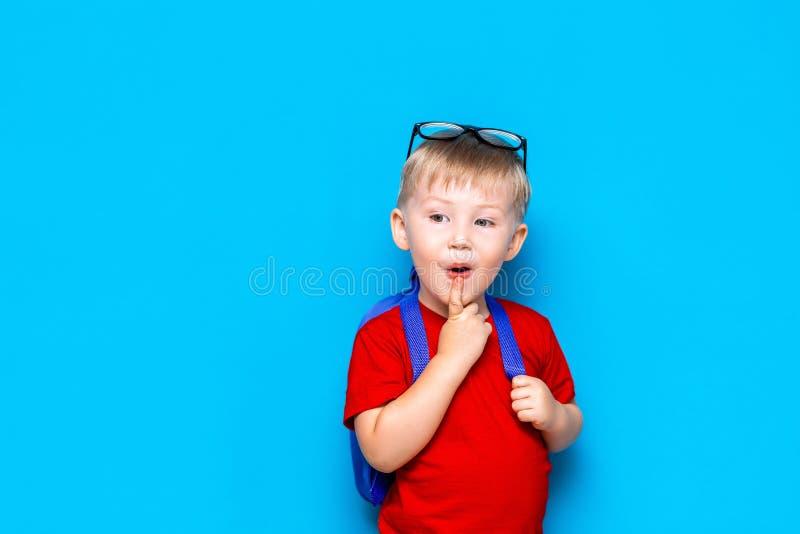 De nouveau au portrait d'école de l'enfant étonné heureux en verres d'isolement sur le fond bleu avec l'espace de copie les nouve images libres de droits