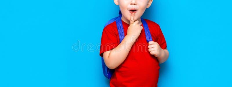 De nouveau au portrait d'école de l'enfant étonné heureux en verres d'isolement sur le fond bleu avec l'espace de copie les nouve image stock