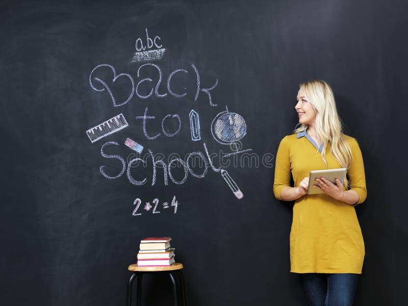 De nouveau au professeur féminin d'école souriant par le tableau noir images libres de droits