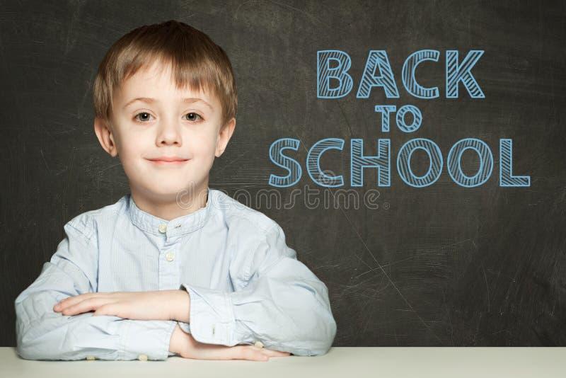 De nouveau au texte d'école et à l'enfant heureux sur le fond de tableau photos stock