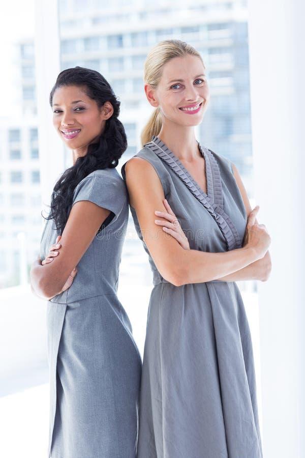 Download De Nouveau Aux Femmes D'affaires Arrières Regardant L'appareil-photo Photo stock - Image du plié, heureux: 56482294