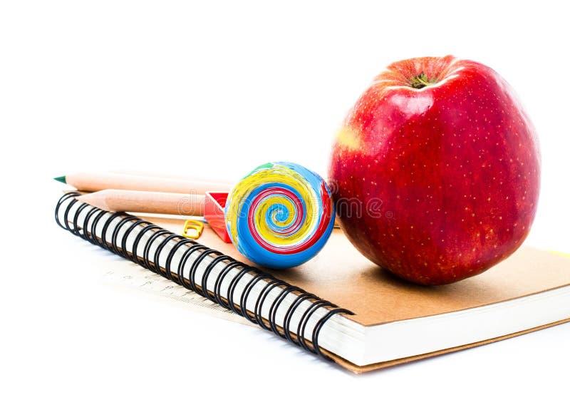De nouveau aux fournitures scolaires avec le carnet et le crayon sur le backg blanc image libre de droits