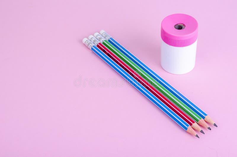 De nouveau ? l'?cole Crayons, taille-crayons sur le fond rose lumineux Place pour le texte photographie stock