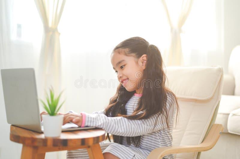 De nouveau ? l'?cole. petite fille asiatique utilisant son ordinateur portable images stock