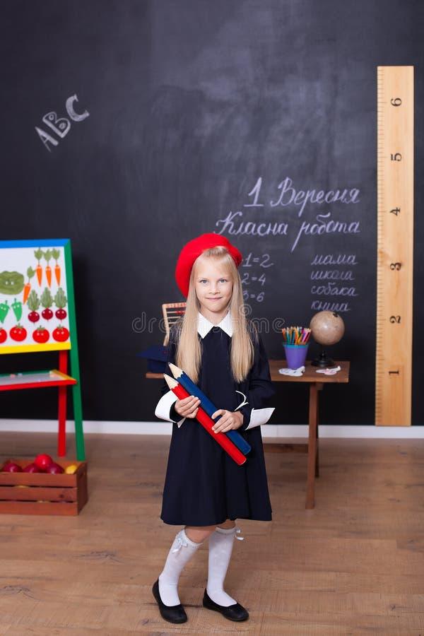 De nouveau ? l'?cole ! Une petite fille se tient avec de grands crayons dans des ses mains ? l'?cole La fille d'?cole r?pond ? la images stock