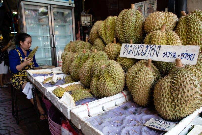 20 de novembro de 2018 - Banguecoque TAILÂNDIA - fruto pealing do Durian da mulher em um mercado em Banguecoque imagem de stock