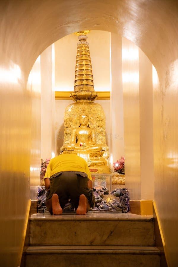20 de novembro de 2018 - Banguecoque TAILÂNDIA - pares que rezam à Buda dourada no templo tailandês foto de stock royalty free