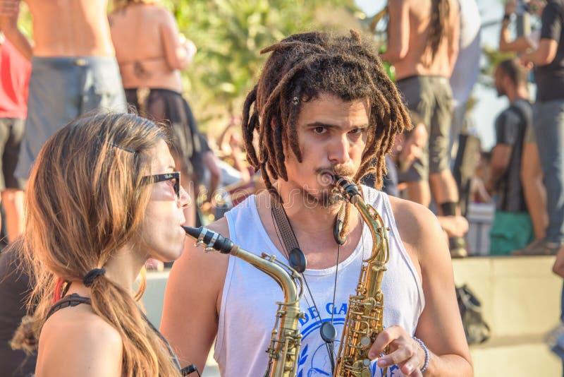 27 de noviembre de 2016 Mujer y hombre con los dreadlocks que tocan los saxofones en la calle en el distrito de Leme, Rio de Jane foto de archivo
