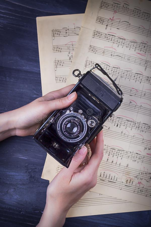 17 de noviembre de 2017 Kraków, Polonia Icono de Zeiss de la cámara del vintage, manos femeninas y notas sobre un fondo oscuro fotografía de archivo libre de regalías