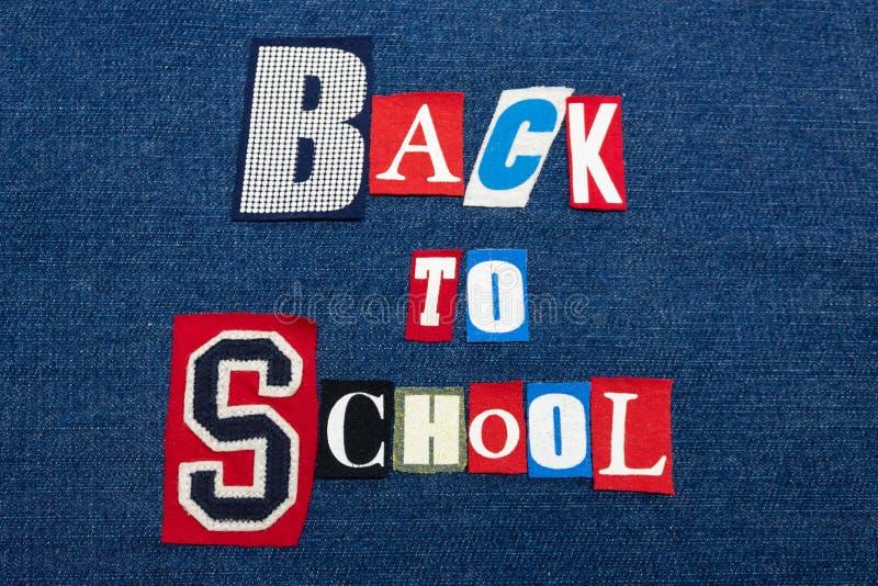 DE NUEVO al collage de la palabra del texto de ESCUELA, tela colorida en el dril de algodón azul, concepto de la educación imagen de archivo libre de regalías
