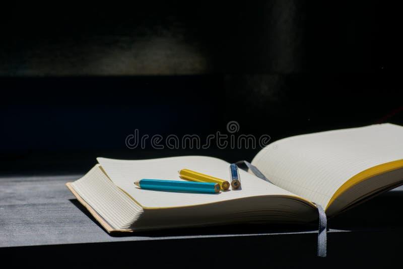 De nuevo al cuaderno amarillo azul del color del lápiz del creyón de Noteblock de la escuela imágenes de archivo libres de regalías