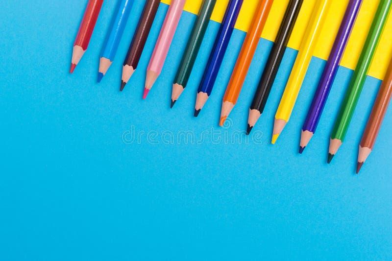 De nuevo al scool - detalle de los l?pices Los lápices agudos coloreados detallan en fila, aislado en azul y amarillo fotos de archivo libres de regalías