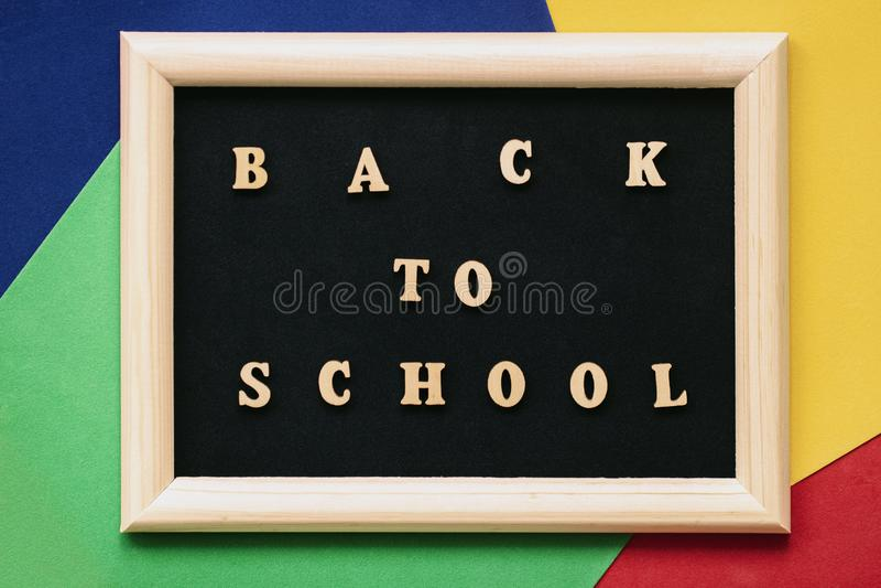 De nuevo al texto de escuela letras de madera escritas en la pizarra negra en marco Concepto de educación, empezando la escuela c foto de archivo