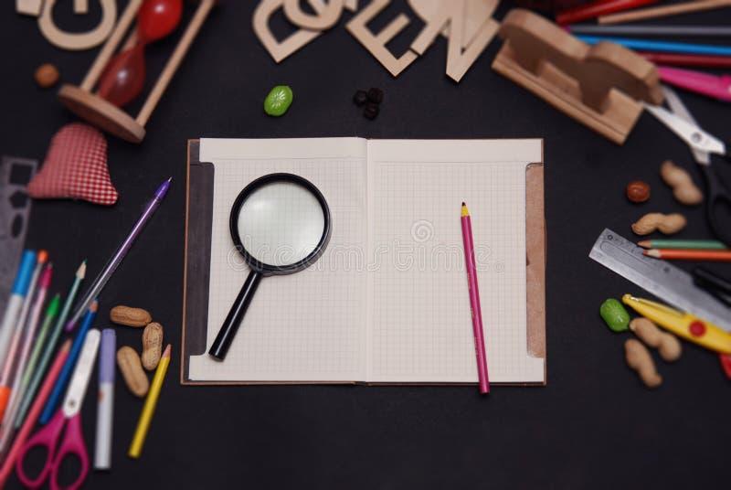 De nuevo a capítulo de la escuela con las fuentes de escuela y el cuaderno abierto, sobre la pizarra fotos de archivo libres de regalías