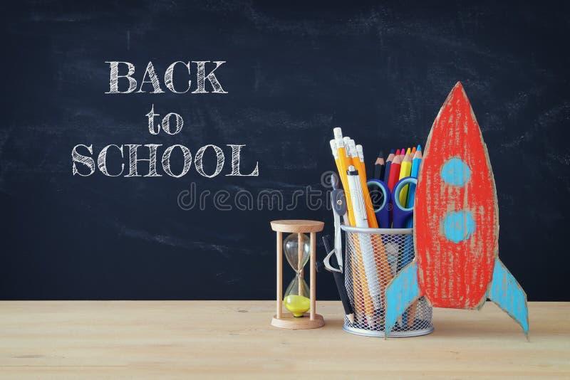 De nuevo a concepto de la escuela cohete y lápices delante de la pizarra de la sala de clase fotografía de archivo libre de regalías