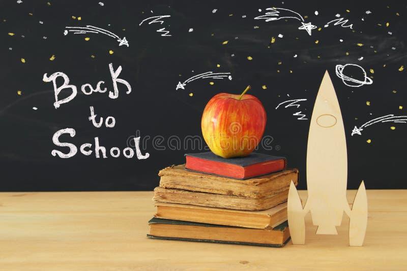 De nuevo a concepto de la escuela cohete y lápices de madera sobre el libro abierto delante de la pizarra de la sala de clase stock de ilustración