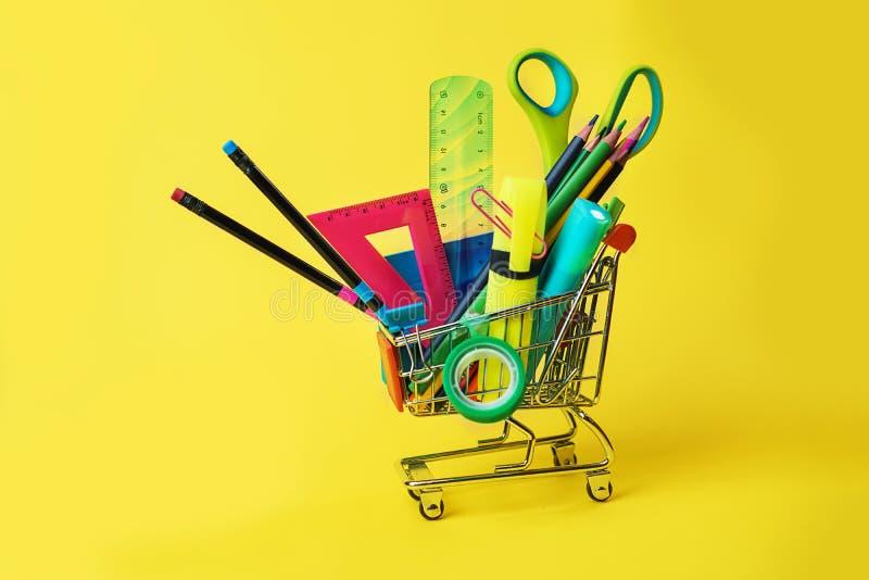 De nuevo a concepto de la escuela con el carro de la compra y los lápices coloridos, regla cuadrada, tijeras, clips, marcadores e foto de archivo libre de regalías