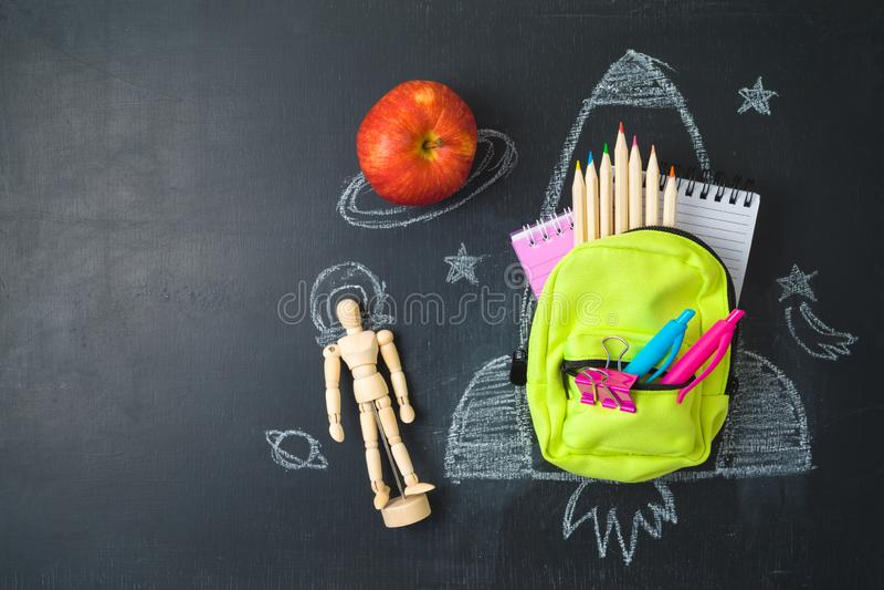 De nuevo a concepto de la escuela con la pequeños mochila del bolso, fuentes de escuela y bosquejo del cohete sobre fondo del cha fotografía de archivo