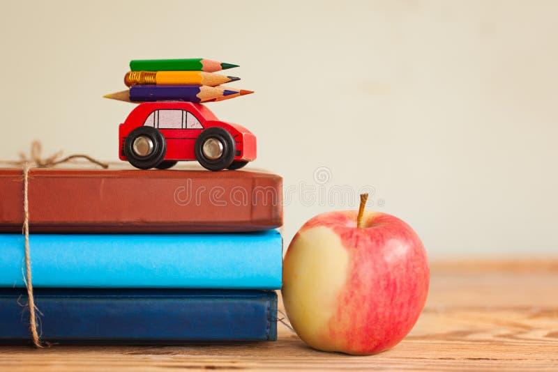 De nuevo a concepto de la escuela con la pila de libros y de coche rojo del manzana y miniatura que llevan el lápiz colorido fotos de archivo