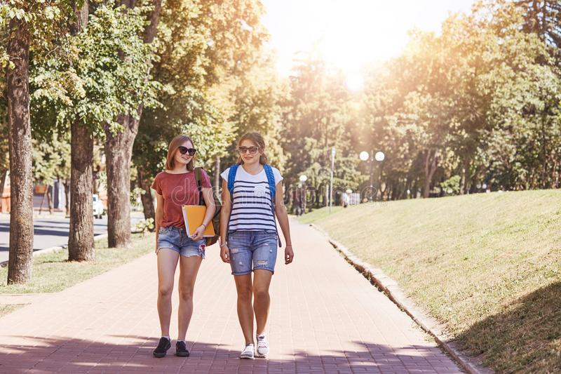 De nuevo a concepto de la escuela Dos estudiantes tienen paseo al aire libre, llevan la mochila y los libros, vestidos en ropa de fotos de archivo