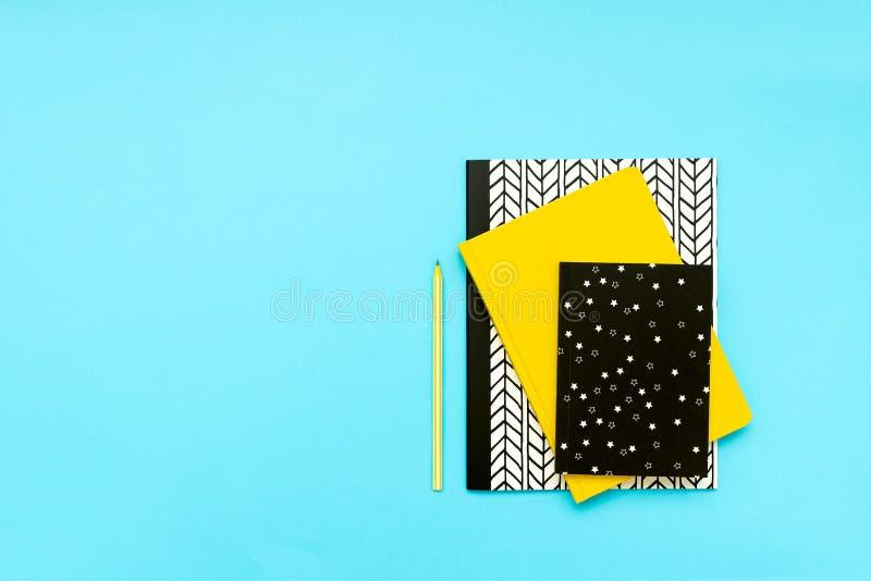 De nuevo a concepto de la escuela Fuentes de escuela: cuadernos y plumas en fondo azul Visi?n superior Copie el espacio Endecha p fotografía de archivo libre de regalías
