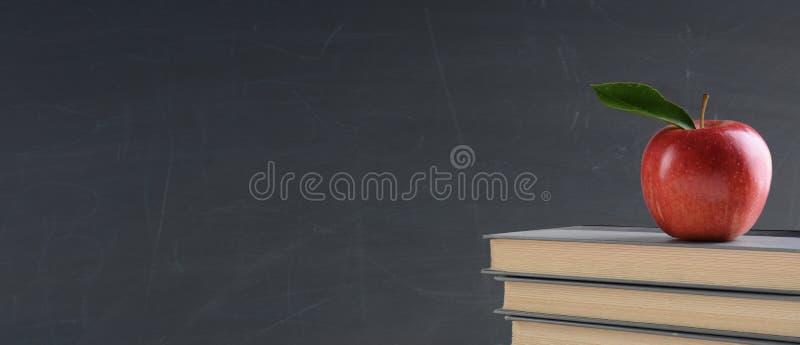 De nuevo a concepto de la escuela: Libros de texto con una manzana roja delante de imagenes de archivo