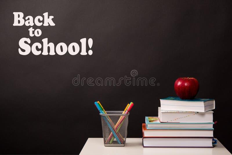 De nuevo a concepto de la escuela, a los libros apilados, a los rotuladores coloreados y a manzana roja fotos de archivo