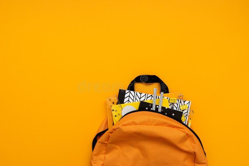 De nuevo a concepto de la escuela Mochila con las fuentes de escuela en fondo amarillo Visi?n superior Copie el espacio Endecha p foto de archivo