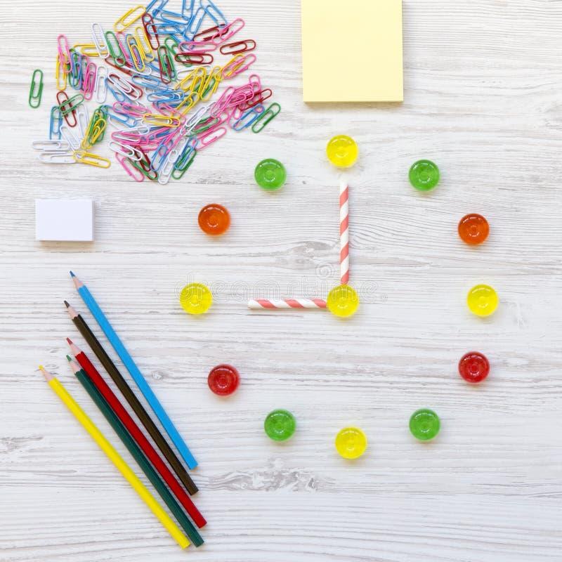 De nuevo a concepto de la escuela Reloj del ` de nueve o en el reloj Reloj hecho de los caramelos dulces coloridos, accesorios pa foto de archivo