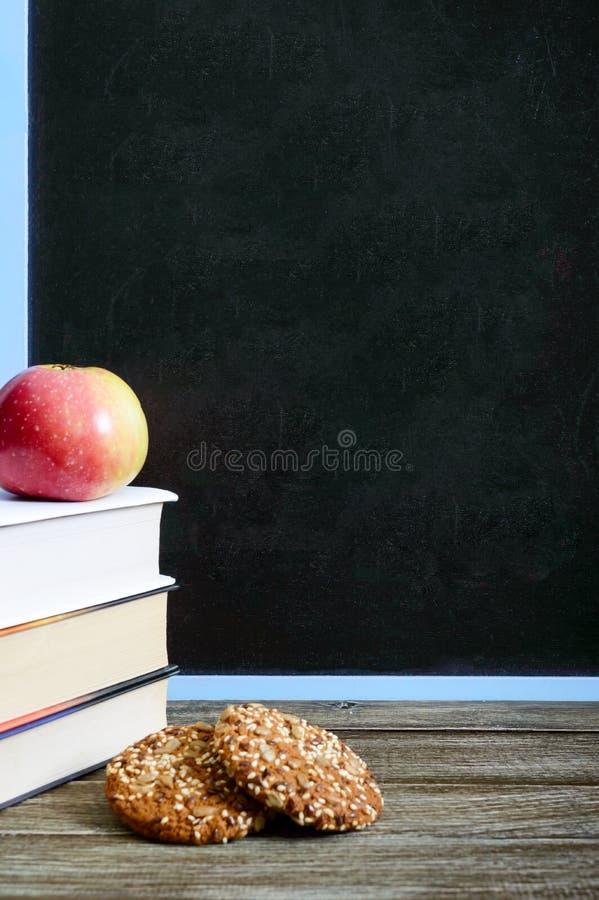 De nuevo a escuela, concepto de la educación Libros, galletas integrales útiles y manzana en la tabla de la sala de clase delante imágenes de archivo libres de regalías