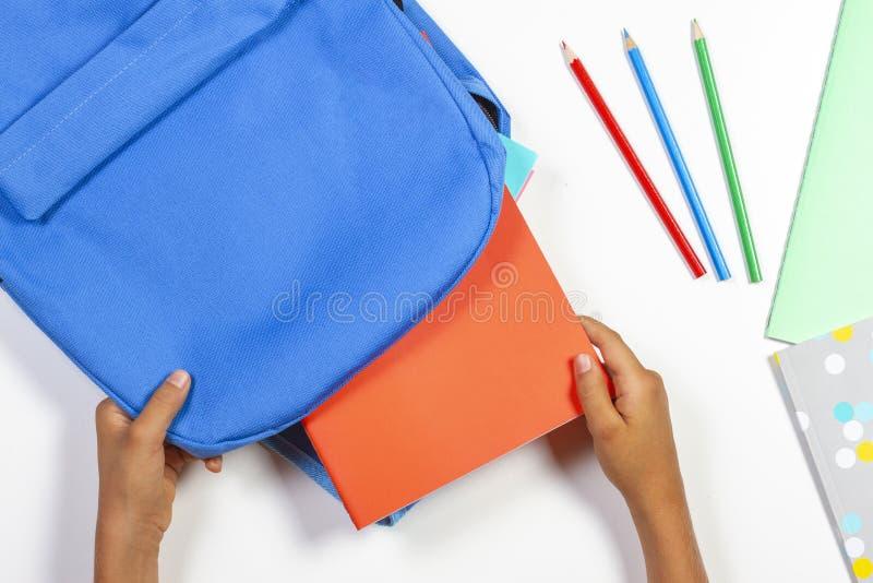 De nuevo a escuela, concepto de la educación Manos del niño que embalan la mochila y que se preparan para la escuela fotografía de archivo libre de regalías