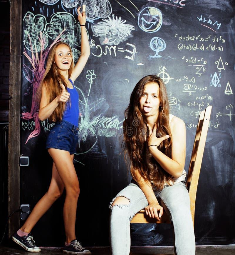 De nuevo a escuela después de vacaciones de verano, dos muchachas adolescentes en sala de clase con la pizarra pintada fotografía de archivo