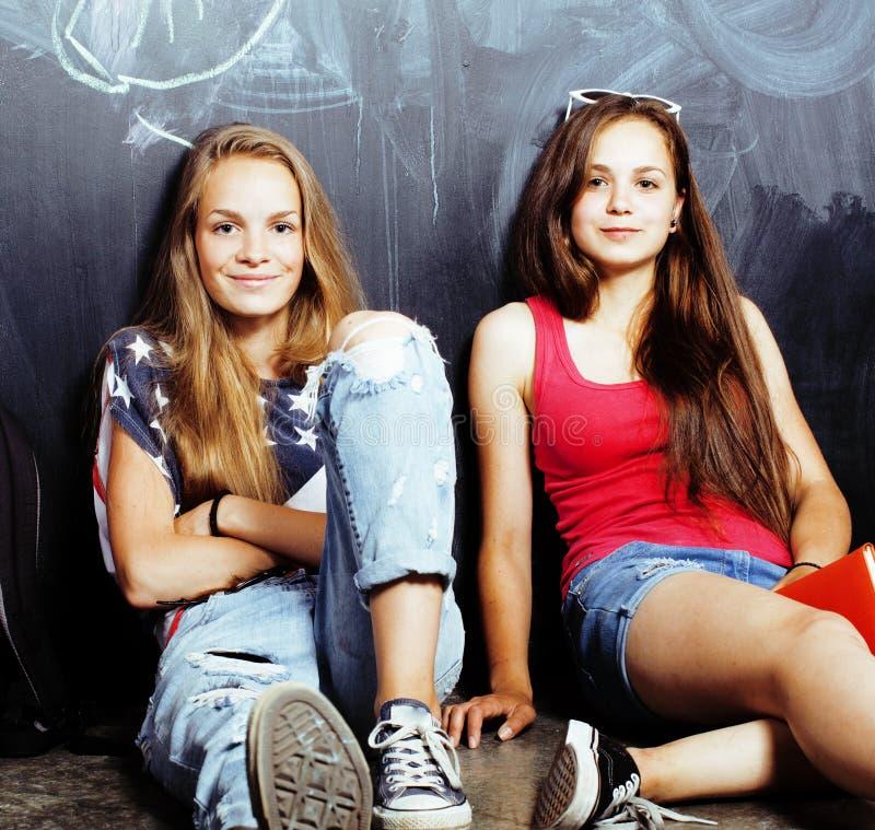 De nuevo a escuela despu?s de vacaciones de verano, dos muchachas reales adolescentes en sala de clase con la pizarra pintada jun fotografía de archivo