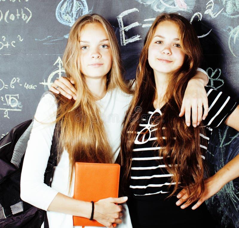 De nuevo a escuela despu?s de vacaciones de verano, dos muchachas reales adolescentes en sala de clase con la pizarra pintada jun foto de archivo libre de regalías