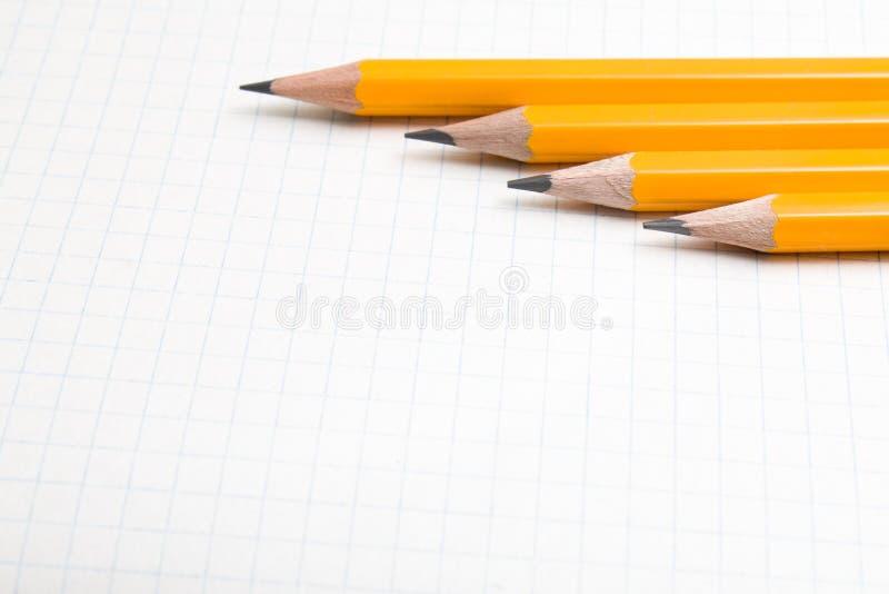 De nuevo a escuela, el concepto de la educación con los lápices anaranjados y el cuaderno en el fondo por nuevo curso académico e fotografía de archivo libre de regalías