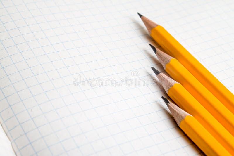 De nuevo a escuela, el concepto de la educación con los lápices anaranjados y el cuaderno en el fondo por nuevo curso académico e foto de archivo libre de regalías