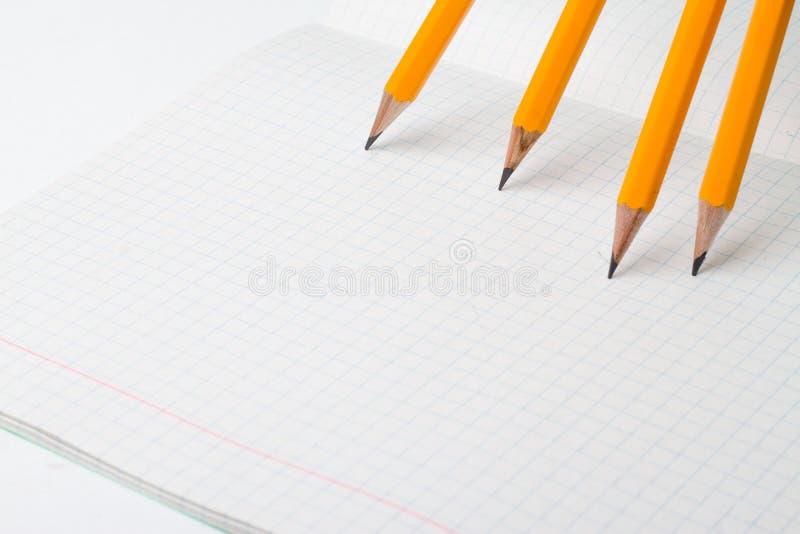 De nuevo a escuela, el concepto de la educación con los lápices anaranjados y el cuaderno en el fondo por nuevo curso académico e fotos de archivo libres de regalías