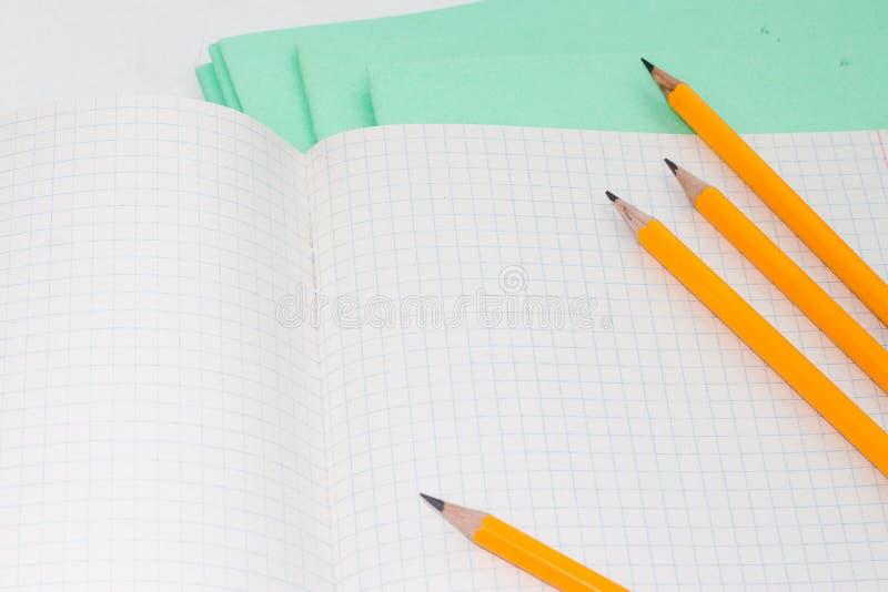 De nuevo a escuela, el concepto de la educación con los lápices anaranjados y el cuaderno en el fondo por nuevo curso académico e foto de archivo