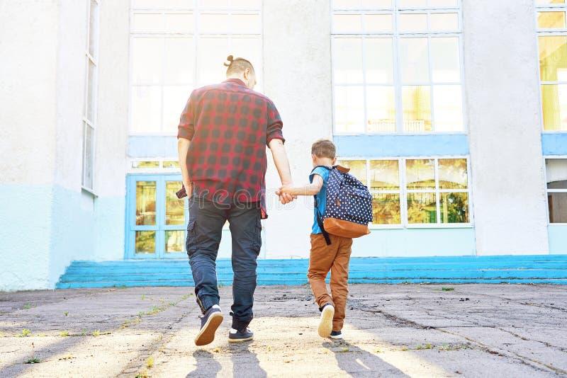 De nuevo a escuela El padre y el hijo felices van a la escuela primaria fotos de archivo