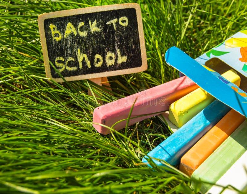 De nuevo a escuela, a la inscripción en el mini-tablero, a la disposición del tablero y a la tiza en la hierba verde, el concepto imágenes de archivo libres de regalías