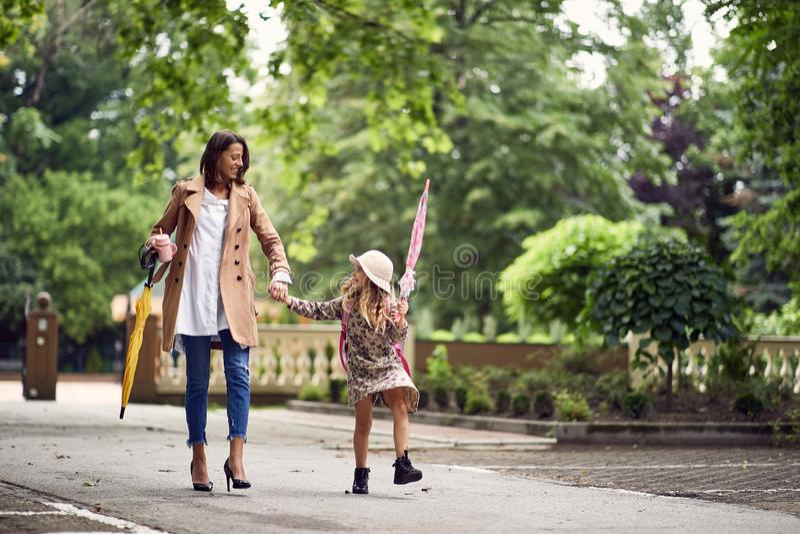 De nuevo a escuela La madre y el daugther felices van a la escuela primaria Padre que lleva al niño a la escuela primaria El alum imagenes de archivo