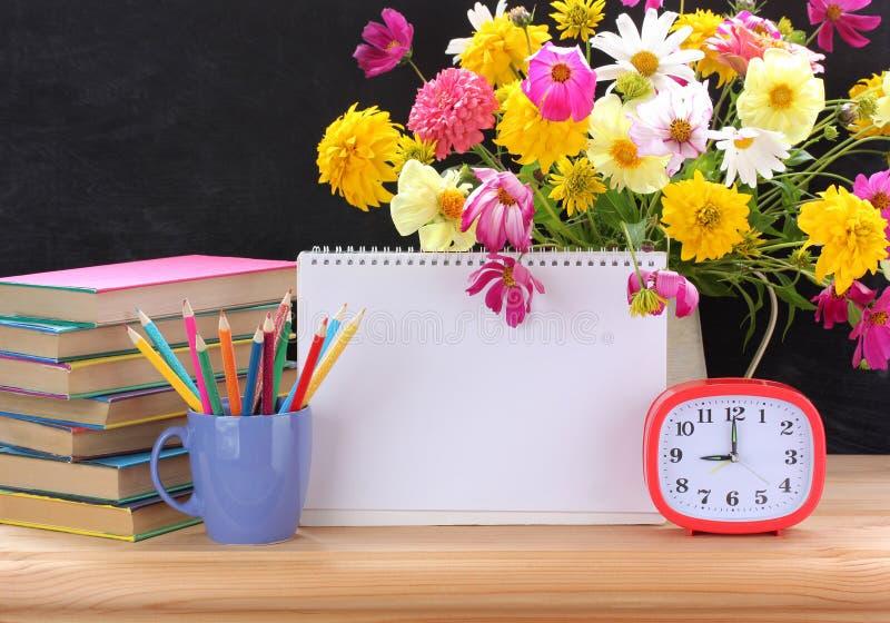 De nuevo a escuela Libros de texto, ramo y despertador Álbum abierto con una página en blanco para su texto imágenes de archivo libres de regalías