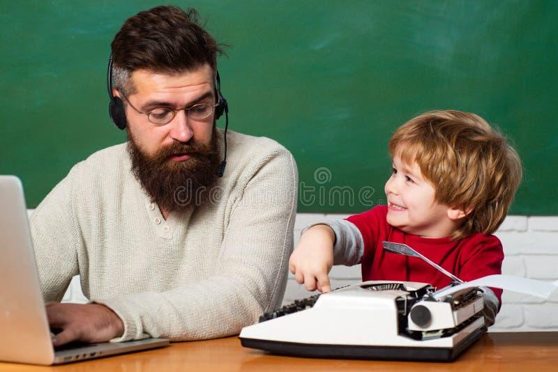 De nuevo a escuela Muchacho joven que hace su preparación de la escuela con su padre Niños de ayuda del profesor con su preparaci imagen de archivo libre de regalías