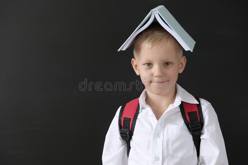 De nuevo a escuela Niño pequeño divertido en la pizarra Niño de la escuela primaria con el libro en su cabeza Concepto de la educ foto de archivo