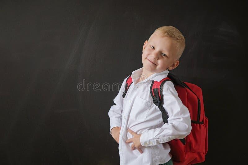De nuevo a escuela Niño pequeño lindo en la pizarra Niño de la escuela primaria con el bolso Concepto de la educaci?n imagen de archivo