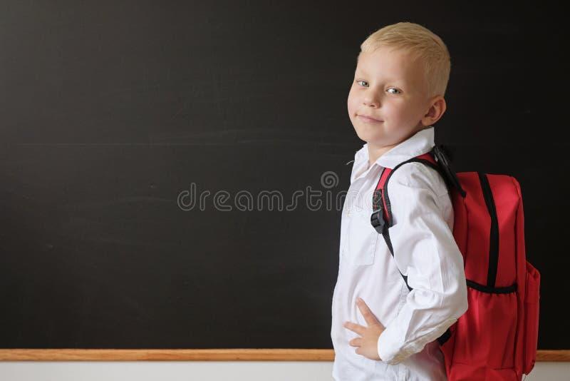 De nuevo a escuela Niño pequeño lindo en la pizarra Niño de la escuela primaria con el bolso Concepto de la educaci?n imagen de archivo libre de regalías
